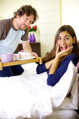 Incredibly happy young cute woman getting breakfast in bed