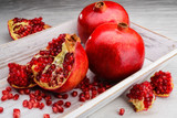 red pomegranate fruits on white wooden background
