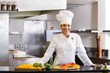 Smiling chef with cut vegetables in kitchen - 61975208