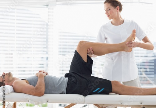 Physiotherapist massaging leg of man