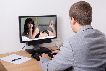 young businessman looking at sexy woman in computer at work