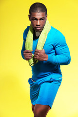Athletic black man in sportswear fashion. Runner with towel. Int