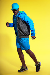 Athletic black man in sportswear fashion. Runner with jacket and
