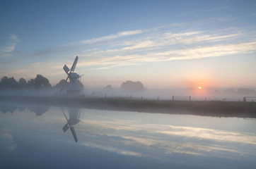 misty sunrise over river and windmill