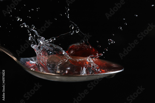 Water drops on air with spoon isolated black bacgraund