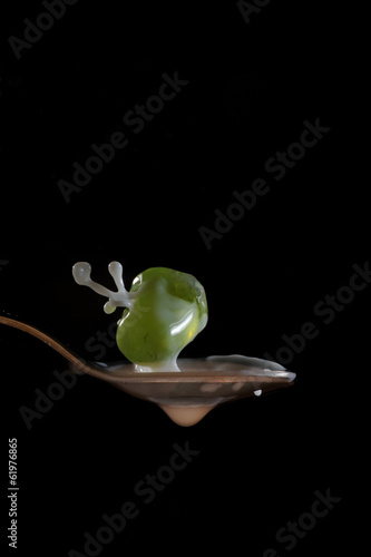 Milk drops on air with spoon isolated black bacgraund