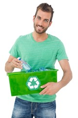 Portrait of a smiling young man carrying recycle container