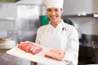 Smiling female chef holding tray of cut meat in kitchen
