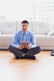 Businessman sitting on the floor using tablet smiling at camera