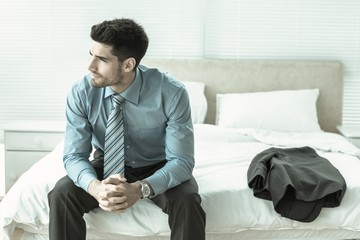 Handsome businessman sitting on bed thinking