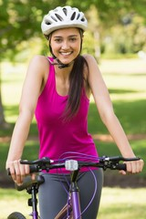 Fit young woman with helmet riding bicycle
