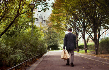 lonely man with shopping bags walk after work