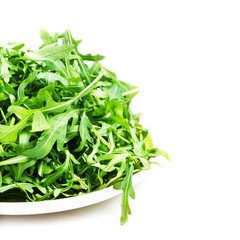 Arugula salad on a plate isolated on white background closeup. H