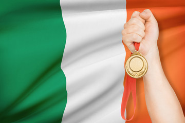 Medal in hand with flag on background - Ireland
