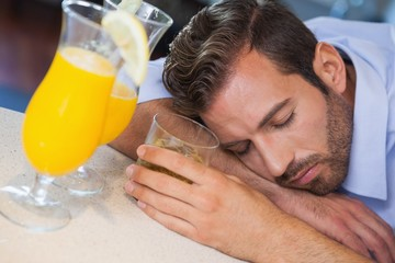 Drunk businessman sleeping on bar beside cocktail