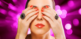woman's face and beautiful red manicure on the red