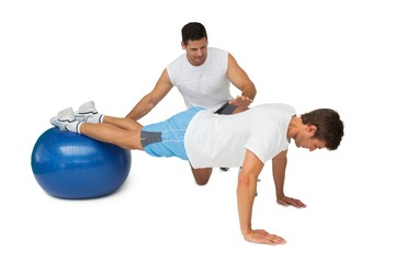 Trainer helping young man exercise on fitness ball