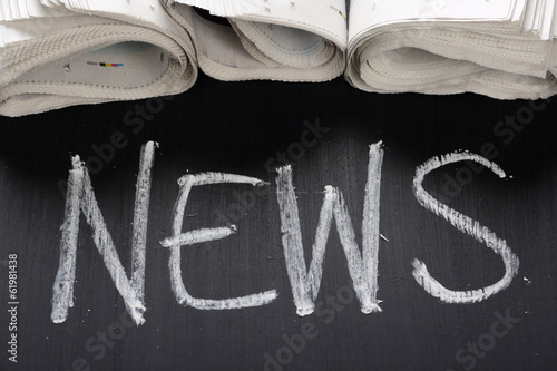The word News written on a blackboard and newspapers
