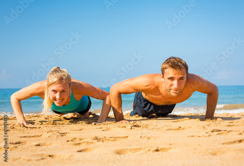 Couple doing push ups on the beach