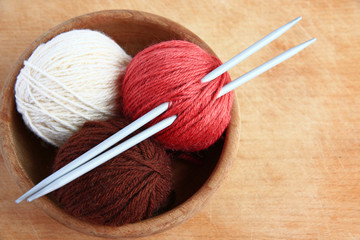 Wool and knitting needles  on wooden background.