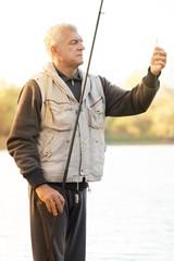 Senior men fishing by the lake.