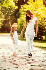 Mother and daughter walking through a park