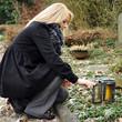 Frau stellt Kerze in Grableuchte