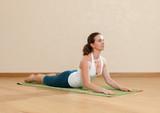 Caucasian woman is practicing yoga at studio (bkhudzhangasana)