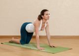 Caucasian woman is practicing yoga at studio (bidalasana)