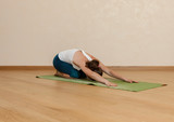 Caucasian woman is practicing yoga at studio (shashankasana)