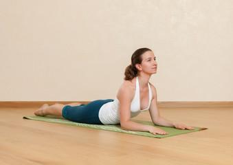 Caucasian woman is practicing yoga at studio (bkhudzhangasana)