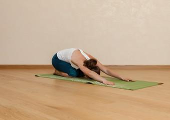 Caucasian woman is practicing yoga at studio (shashankasana)
