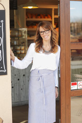 Small coffee shop owner woman standing in facade