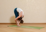 Caucasian woman is practicing yoga at studio (padahastasana)