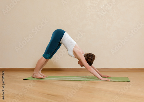 Caucasian woman is practicing yoga at studio (mukha svanasana)