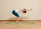 Caucasian woman is practicing yoga at studio (utkatasana)