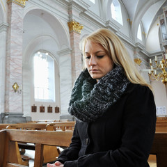 Frau trauert in Kirche