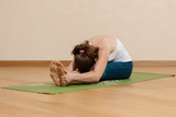 Caucasian woman is practicing yoga at studio (pashchimottanasana