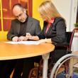 Frau mit Rollstuhl bei Besprechnung im Büro