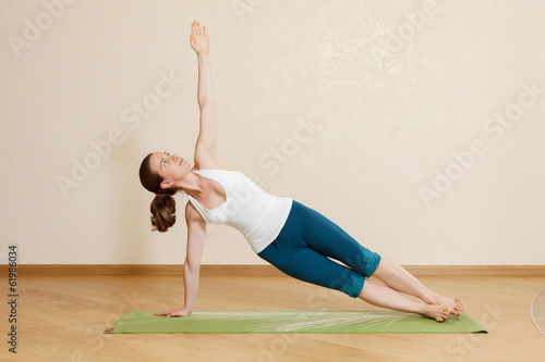 Caucasian woman is practicing yoga at studio (vasishtkhasana)