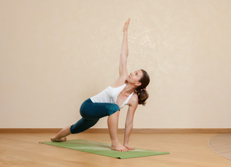 Caucasian woman is practicing yoga at studio (utthita parsvokona