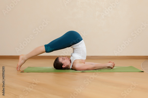 Caucasian woman is practicing yoga at studio (halasana)