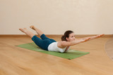 Caucasian woman is practicing yoga at studio (makarasana)