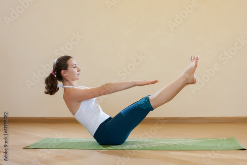 Caucasian woman is practicing yoga at studio (paripurna navasana