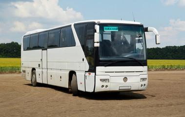 Заказной междугородний автобус, стоящий на проселочной дороге