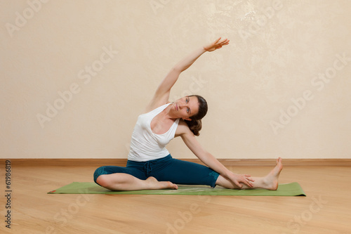 Caucasian woman is practicing yoga at studio (parivrtta janu sir