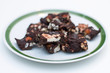 Homemade Rocky road chocolate on white plate with green trim on