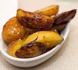 Oven baked potatoes in white bowl on beige