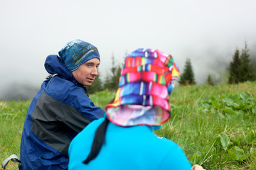Hikers talk while rest in mountains