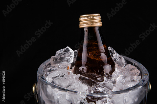 A bottle of refreshing drink chilled in an ice bucket